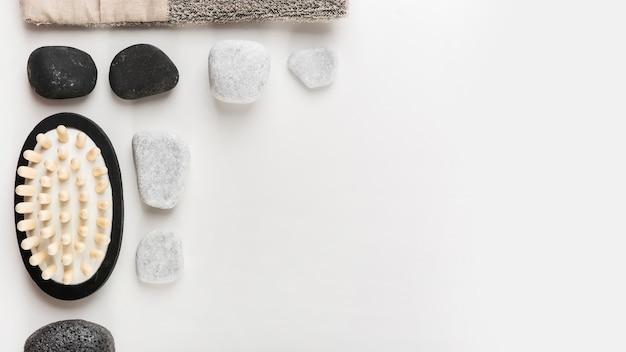 Une vue de dessus de la brosse de massage; pierre spa et pierre ponce sur fond blanc
