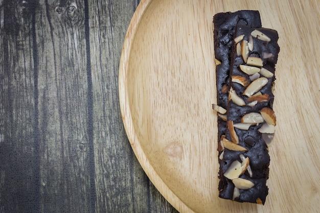Vue de dessus des brownies au chocolat gâteau aux noix sur une plaque en bois et fond en bois.