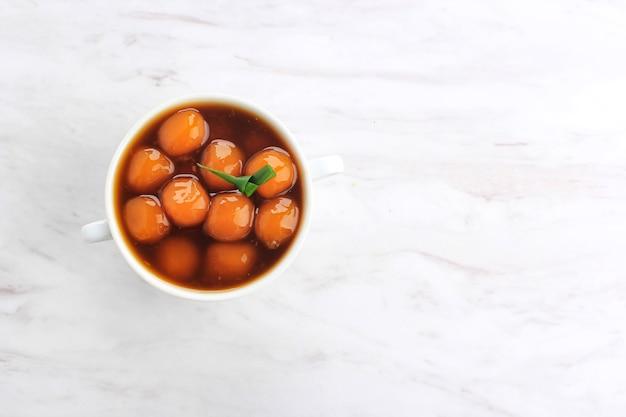 Vue de dessus bubur biji salak (candil) est un dessert indonésien célèbre pendant le petit-déjeuner du ramadan. fabriqué à partir de boules de kabocha de patate douce ou de citrouille jaune avec du sirop de sucre de palme et du lait de coco.