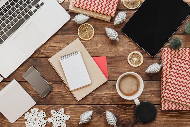 Vue de dessus d'un bureau en bois avec ordinateur avec fournitures de bureau et décorations de noël