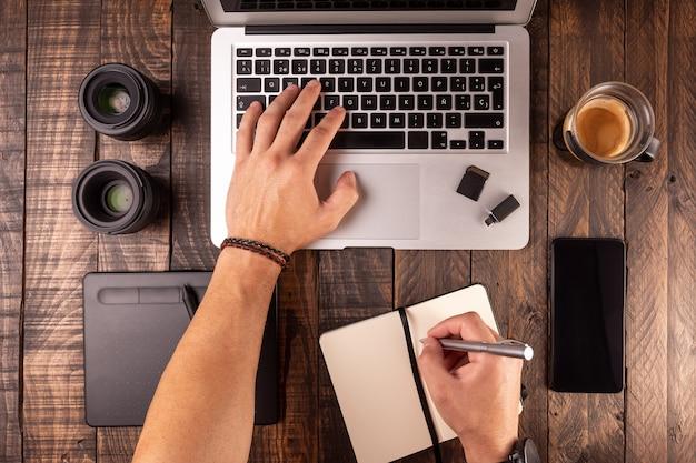 Vue de dessus de bureau en bois avec ordinateur portable, table, café, ordinateur portable, mobile, cartes mémoire.