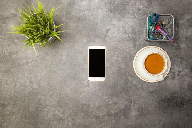 Vue de dessus de bureau avec café, plante en pot, téléphone portable et accessoires professionnels