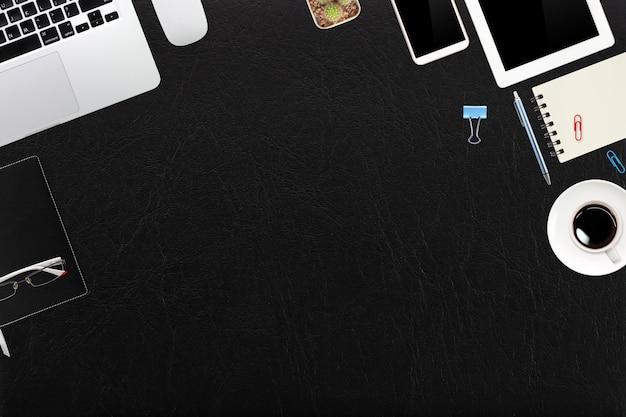 Vue de dessus bureau en cuir noir avec ordinateur, fournitures de bureau, téléphone portable, tablette et café