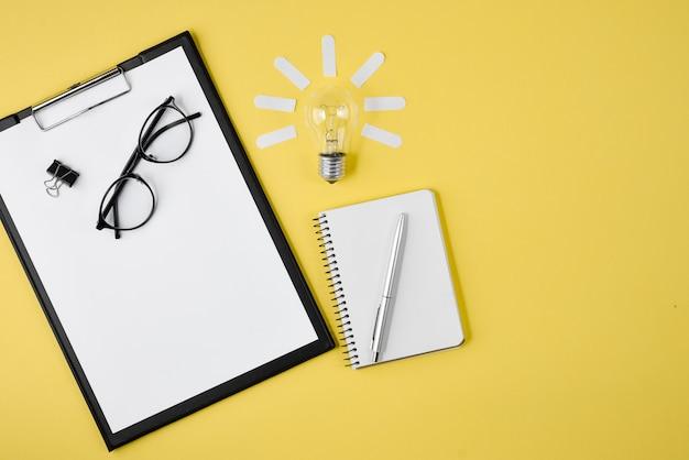 Vue de dessus de bureau espace de travail de style design fournitures de bureau avec stylo, bloc-notes, lunettes, ampoule