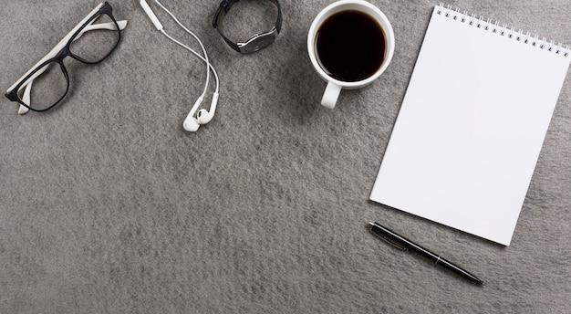 Une vue de dessus d'un bureau gris avec des fournitures de bureau; accessoires personnels et tasse à café