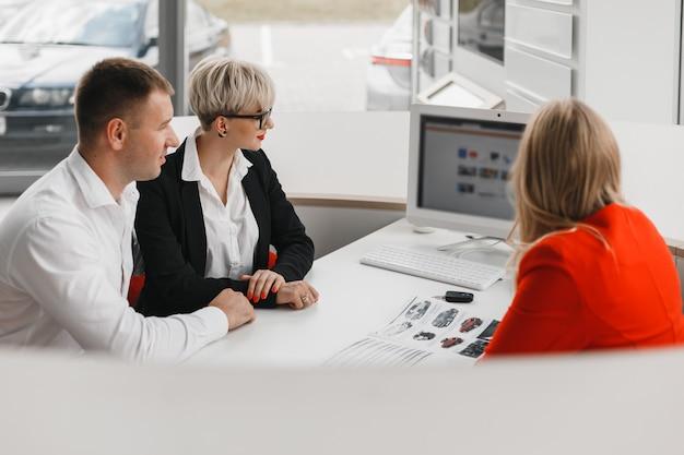 Vue de dessus d'un bureau lors d'une transaction entre un concessionnaire et un couple familial qui achète une voiture