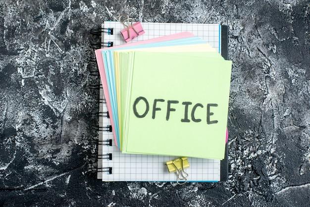 Vue de dessus bureau note écrite avec des autocollants colorés et un cahier sur fond gris