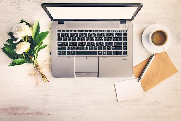 Vue de dessus d'un bureau avec ordinateur, enveloppe, note vide et un bouquet de fleurs de pivoine.