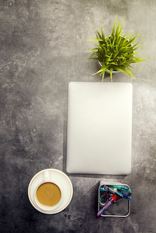 Vue de dessus de bureau avec ordinateur portable, café, plante en pot et accessoires