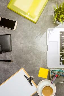 Vue de dessus de bureau avec ordinateur portable, café, plante en pot, fichier de document, téléphone portable et accessoires professionnels
