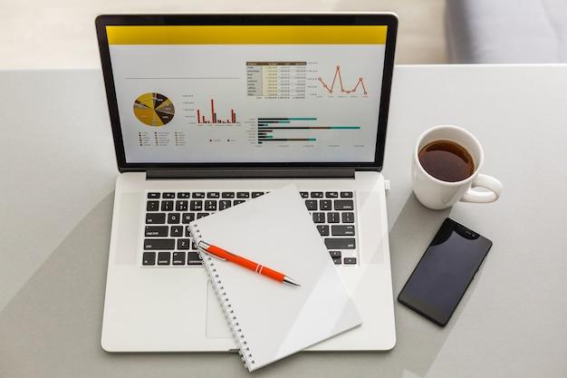 Vue de dessus bureau avec ordinateur portable, crayon et plante en pot sur blanc