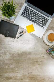 Vue de dessus de bureau avec ordinateur portable, ordinateur portable, pense-bête, café, plante en pot et accessoires