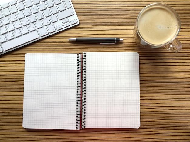 Vue de dessus de bureau. ordinateur portable, stylo et ordinateur portable sur le mur du bureau en bois.