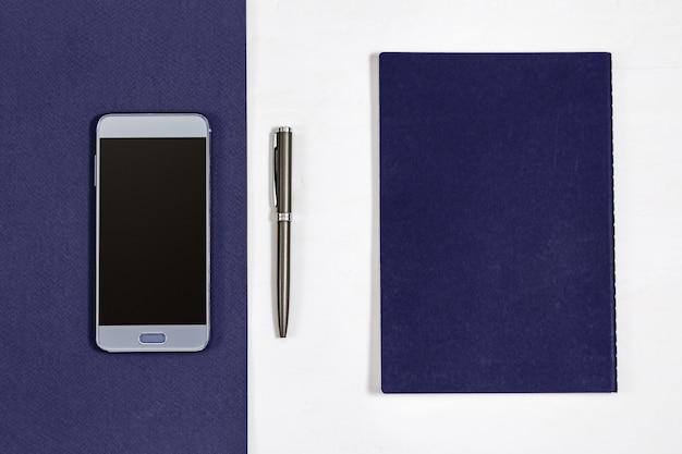 Vue de dessus sur le bureau avec smartphone, cahier, stylo.