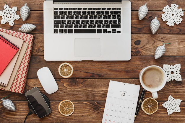 Vue de dessus d'un bureau de surface en bois avec ordinateur avec fournitures de bureau et décorations de noël