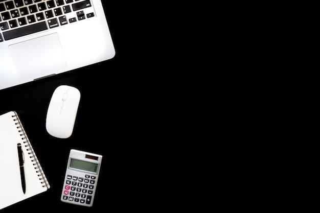 Vue de dessus bureau table bureau. espace de travail avec calculatrice, stylo, ordinateur portable, notez le noir