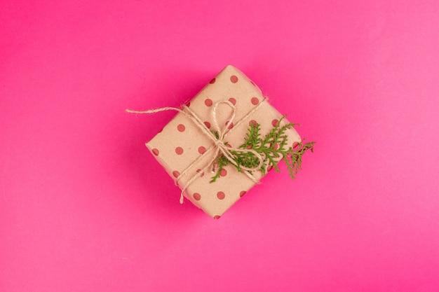 Vue de dessus d'un cadeau décoré avec un arc sur fond rose