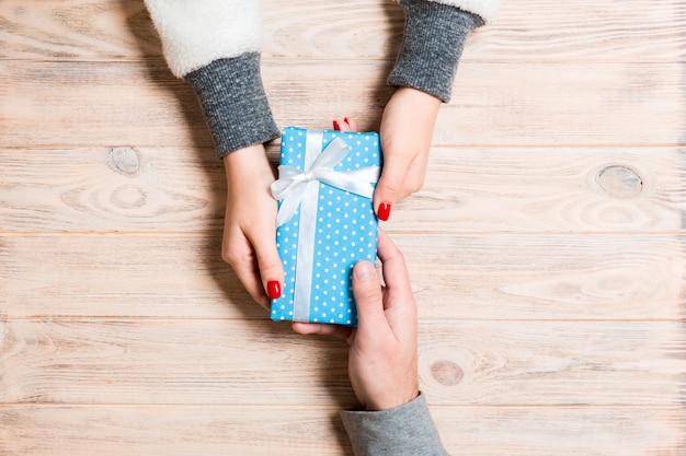 Vue de dessus d'un cadeau entre des mains masculines et féminines