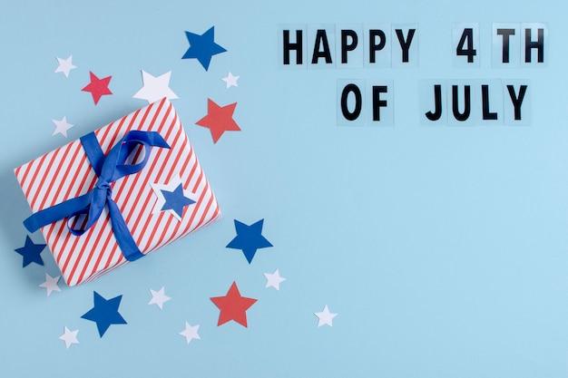 Vue de dessus cadeau enveloppé du drapeau des états-unis avec des lettres du 4 juillet et un espace de copie