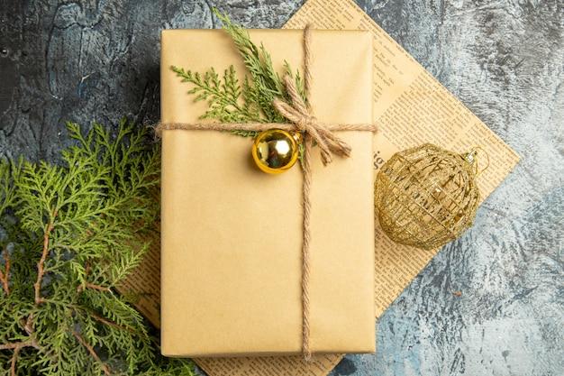 Vue de dessus cadeau de noël sur des branches de pin journal jouet de noël sur une surface grise