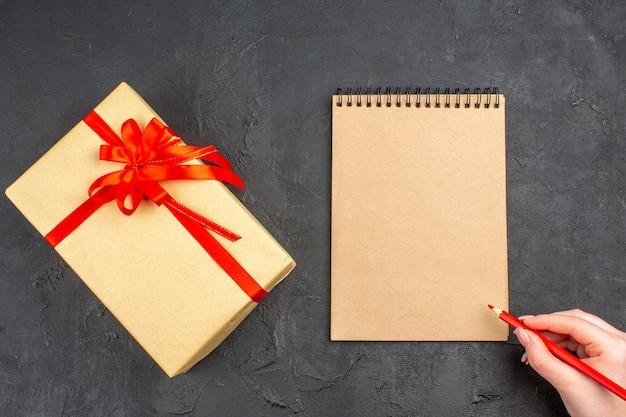 Vue de dessus cadeau de noël en papier brun attaché avec un stylo pour ordinateur portable à ruban rouge dans une main féminine sur fond sombre