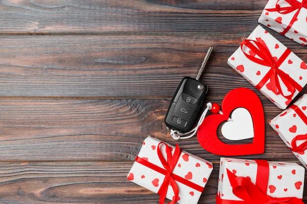 Vue de dessus d'un cadeau pour la saint-valentin, clé de voiture et coeurs de jouets en bois