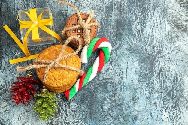 Vue de dessus cadeaux de noël biscuits liés bonbons de noël sur l'espace libre de surface grise