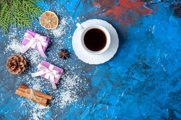 Vue de dessus cadeaux de noël branches de sapin cônes anis sur fond bleu place libre