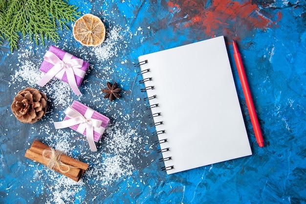 Vue de dessus cadeaux de noël branches de sapin cônes anis sur surface bleue