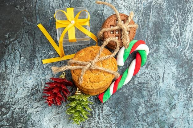 Vue de dessus des cadeaux de noël liés aux biscuits coffret de bonbons de noël sur la surface grise