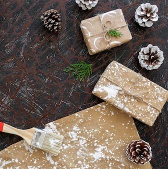 Vue de dessus des cadeaux de noël avec pinceau et pommes de pin