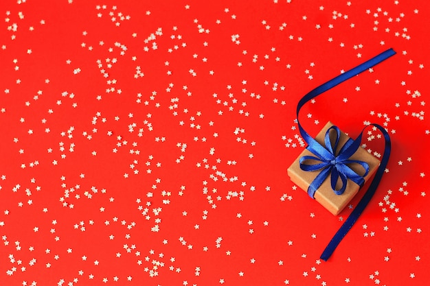 Vue de dessus sur les cadeaux de noël avec ruban sur fond de papier rouge avec des étoiles d'argent. fond