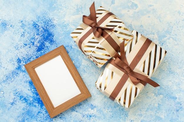 Vue de dessus cadeaux saint valentin cadre vide sur bleu blanc grunge