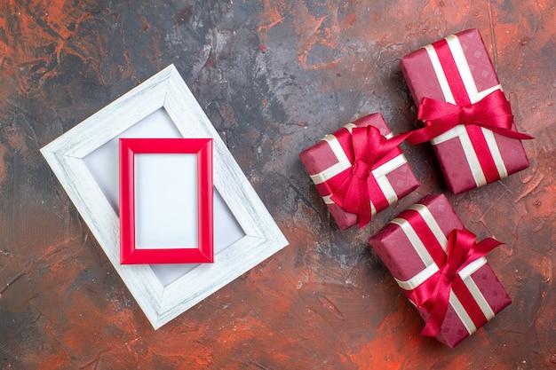 Vue de dessus des cadeaux de la saint-valentin dans un emballage rouge sur une photo de couleur de surface sombre je t'aime cadeau sentiment d'amour