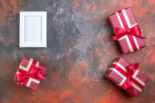 Vue de dessus des cadeaux de la saint-valentin dans un emballage rouge sur une surface sombre cadeau photo d'amour amour je t'aime sentir la couleur