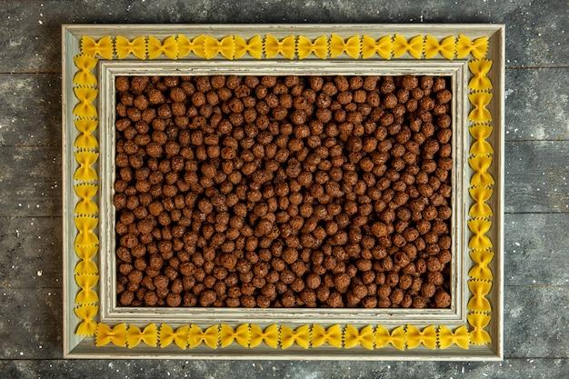 Vue de dessus d'un cadre photo en bois avec des pâtes farfalle et rempli de boules de maïs aux céréales au chocolat