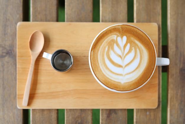 Vue de dessus café au lait chaud avec motif coeurs et sirop sur table en bois