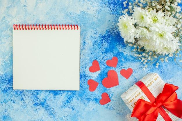 Vue de dessus cahier de fleurs blanches petit cadeau coeurs rouges sur fond bleu