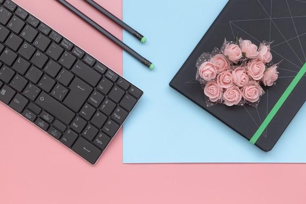 Vue de dessus, cahier avec des fleurs et un crayon avec clavier sur fond rose et bleu.