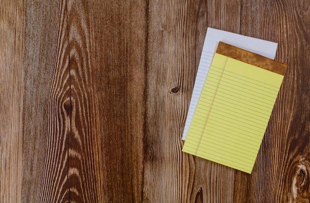 Vue de dessus d'un cahier ouvert avec fond de bureau en bois bloc-notes à plat
