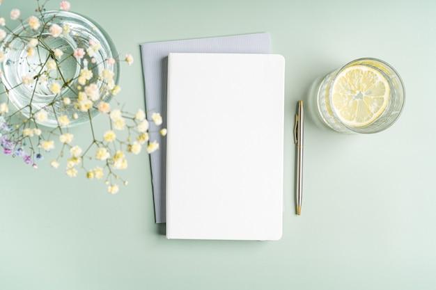 Vue de dessus cahier de papier vierge, fleurs, eau au citron et stylo. mise à plat