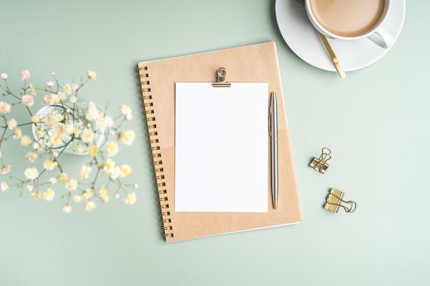 Vue de dessus cahier de papier vierge, fleurs, trombones en papier doré, tasse de café et stylo. mise à plat