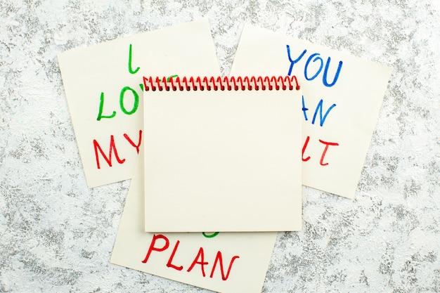 Vue de dessus cahier à spirale et papiers avec des phrases inspirantes sur fond bleu