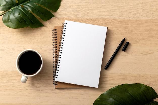 Vue de dessus des cahiers avec des feuilles et une tasse de café