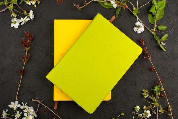 Vue de dessus des cahiers jaunes autour de fleurs blanches sur le sol sombre