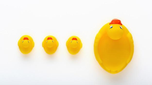Vue de dessus de canetons jaunes jouet avec canard mère sur fond blanc, concept de famille