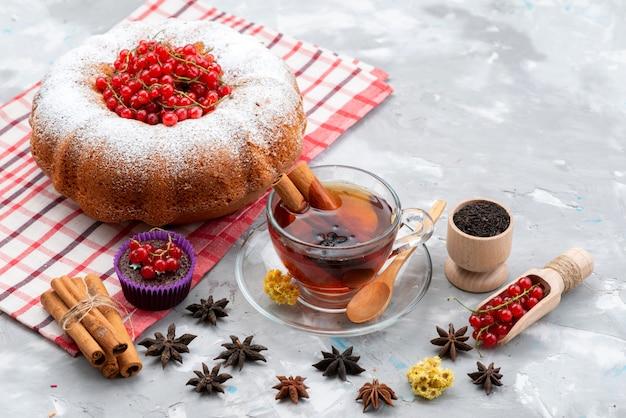 Une vue de dessus de canneberges rouges fraîches aigre-doux et moelleux avec du thé gâteau rond et de la cannelle sur le bureau blanc couleur fraîche