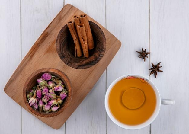 Vue de dessus de la cannelle avec des boutons de rose séchés dans des bols sur une planche avec une tasse de thé sur une surface blanche