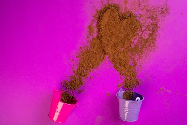 Vue de dessus de la cannelle en poudre éparpillée à partir de petits seaux en forme de coeur sur violet