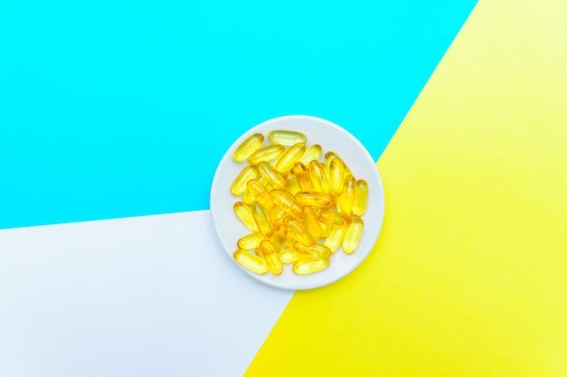 Vue de dessus des capsules de gel d'huile de poisson oméga-3 sur une plaque blanche sur fond blanc, bleu et jaune. concept de soins de santé créatif